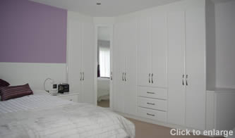 White fitted bedroom furniture with inset mirrors