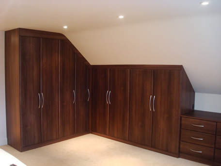 Fitted wardrobes in walnut with sloping ceiling