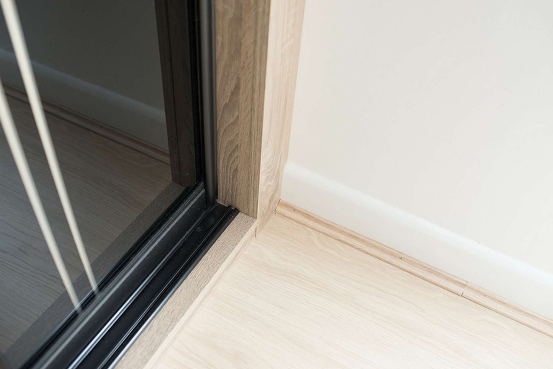 Close up of sliding wardrobe plinth and track