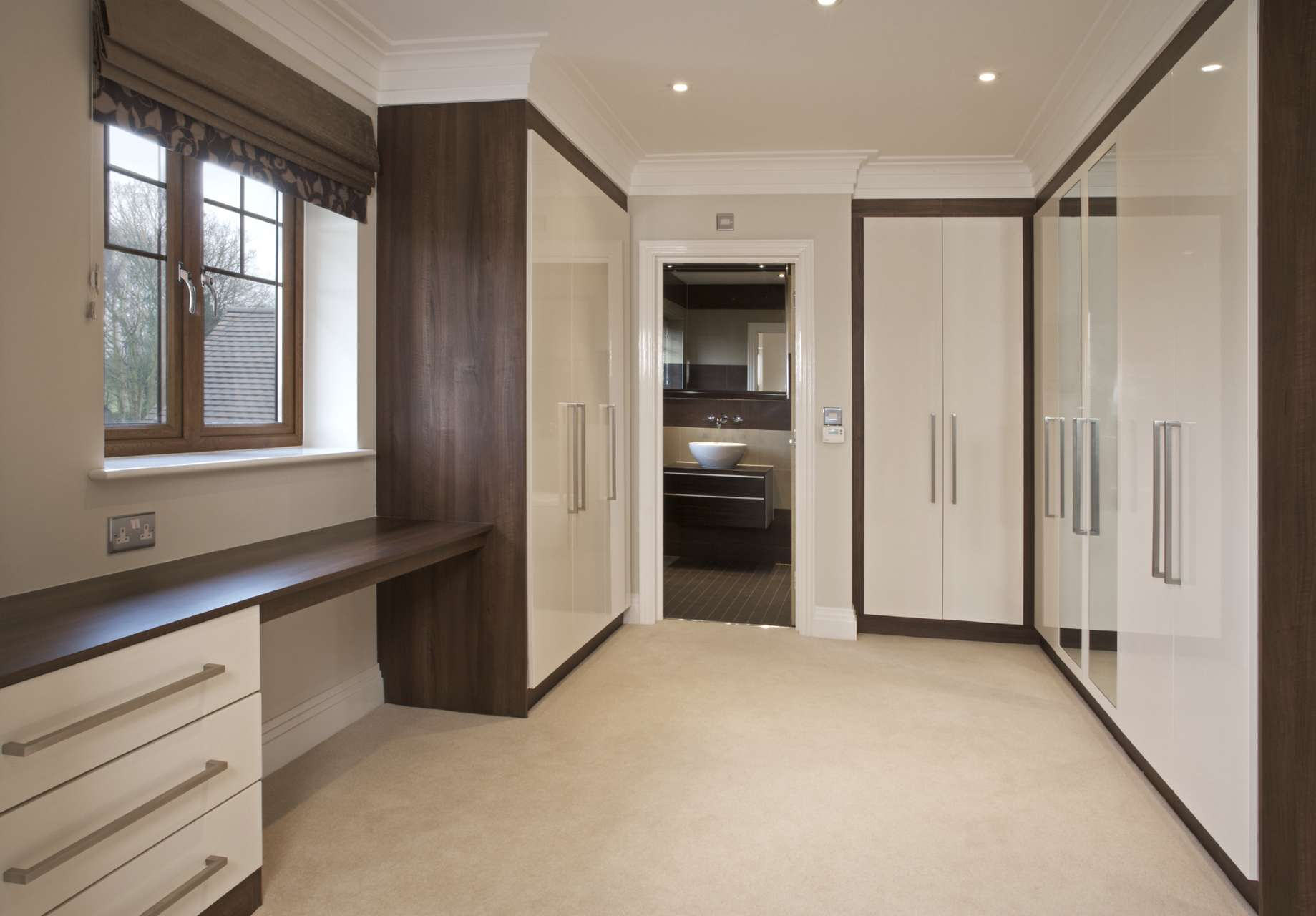 A walk in wardrobe with hinged doors